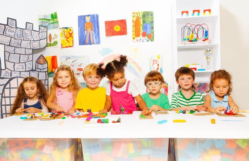 Crianças no jogo tornando-se da classe com plasticine imagem de stock royalty free