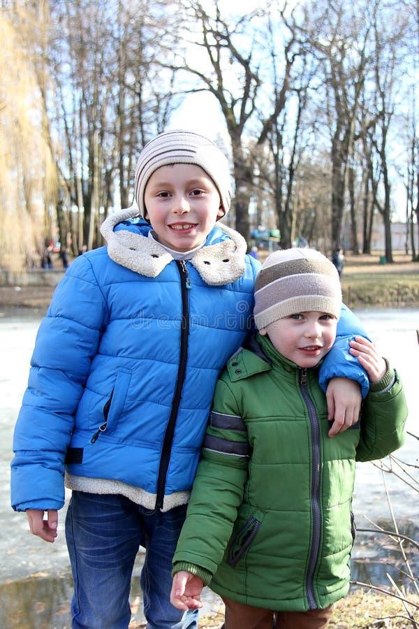 Crianças no parque em uma caminhada no fundo do lago congelado foto de stock royalty free