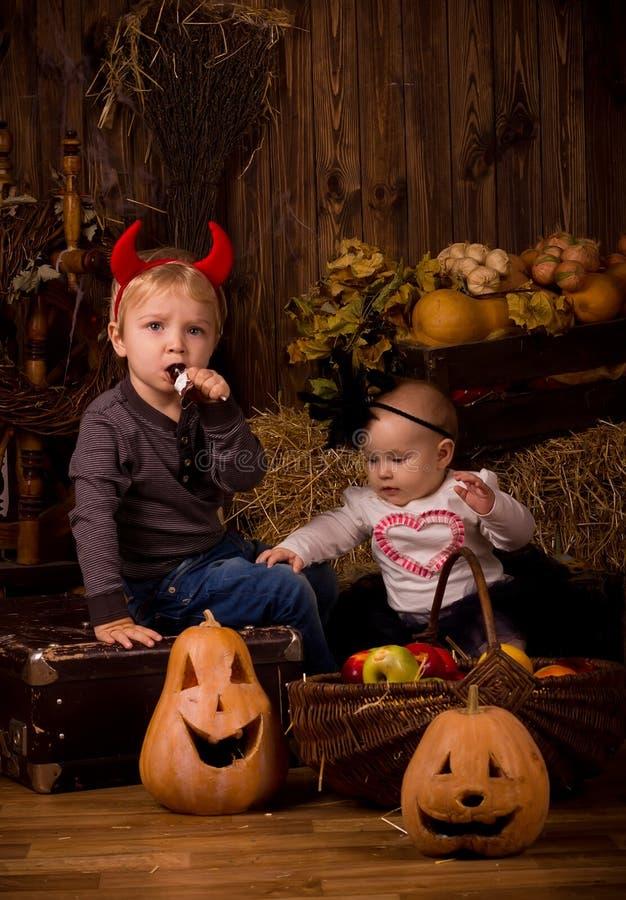 Crianças no partido de Dia das Bruxas com abóboras fotografia de stock