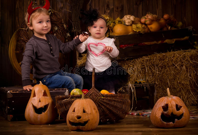 Crianças no partido de Dia das Bruxas com abóboras fotos de stock