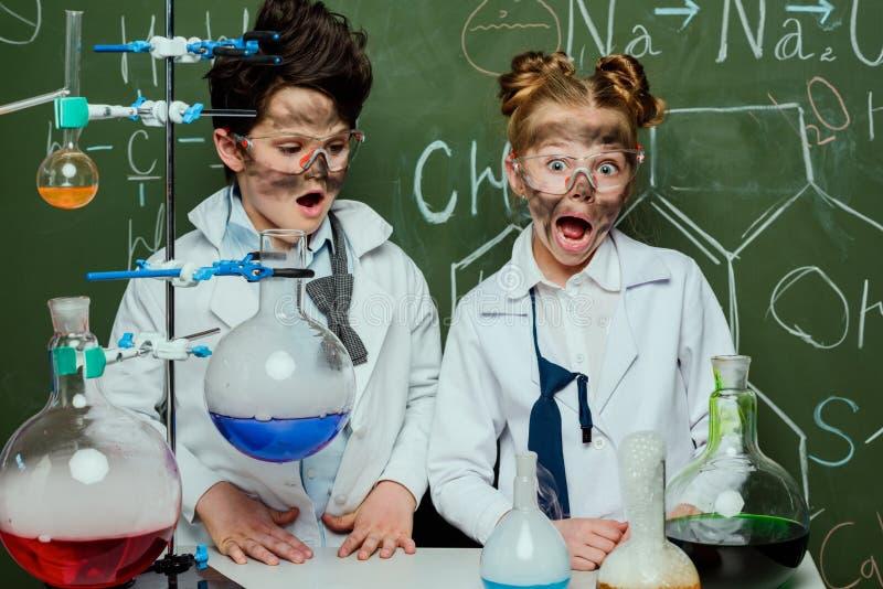 Crianças nos revestimentos brancos com quadro atrás no laboratório de ciência imagens de stock