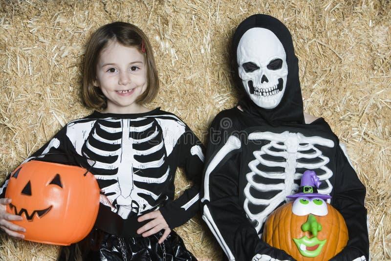 Crianças nos trajes de esqueleto que guardam Jack-O-lanternas foto de stock royalty free
