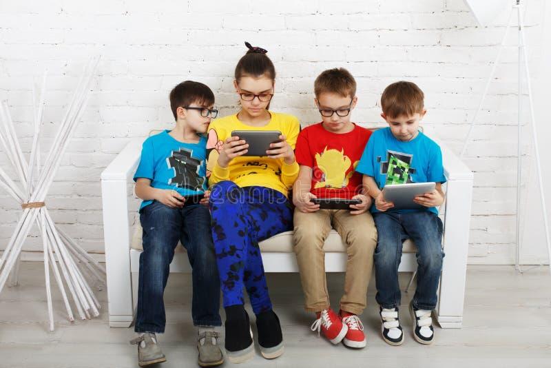 Crianças nos vidros com dispositivos, apego do computador imagens de stock royalty free