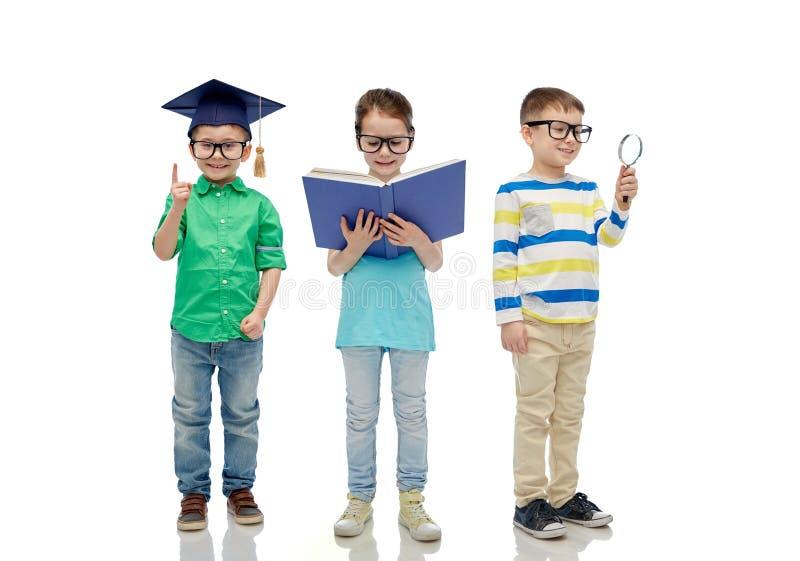 Crianças nos vidros com o chapéu do livro, da lente e do licenciado imagens de stock royalty free