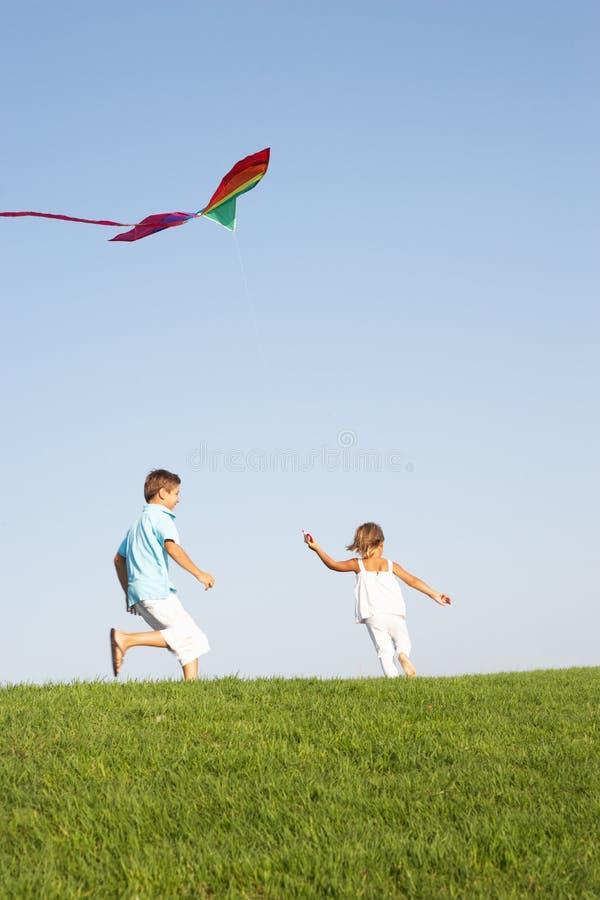 Crianças novas funcionadas com papagaio fotos de stock