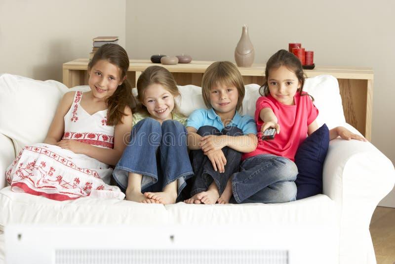 Crianças novas que prestam atenção à televisão em casa imagem de stock royalty free