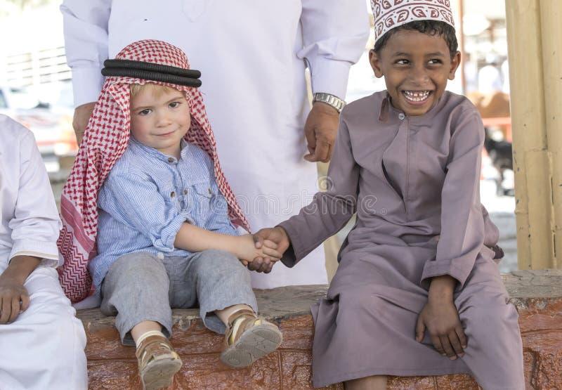 Crianças omanenses e europeias que fazem amigos fotos de stock