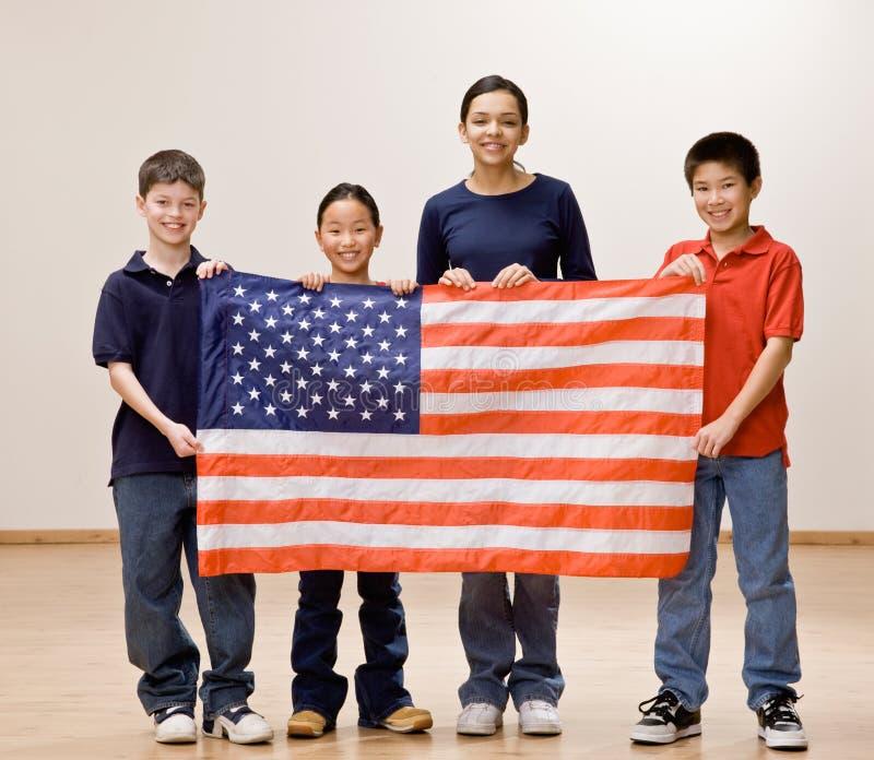 Crianças patrióticas que sustentam a bandeira americana foto de stock royalty free