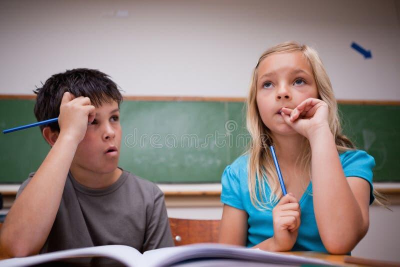 Crianças pensativas que trabalham junto imagem de stock