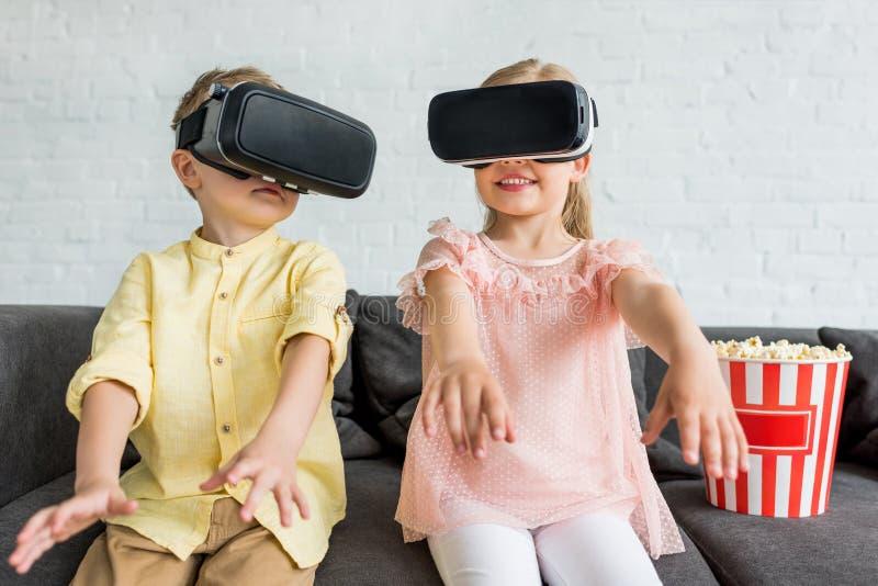 crianças pequenas adoráveis que usam auriculares da realidade virtual ao sentar-se no sofá imagens de stock