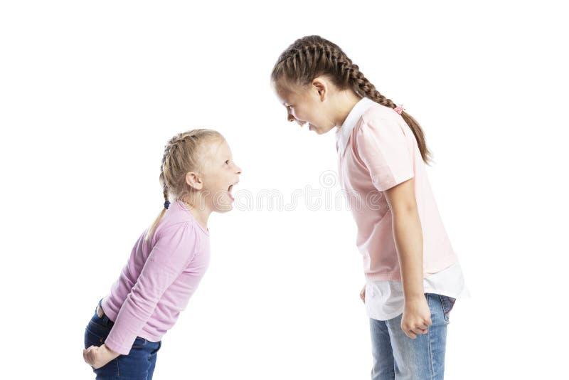 Crianças pequenas, amigas em camisetas cor-de-rosa e grito das calças de brim em se Raiva e esfor?o Isolado sobre o fundo branco imagens de stock royalty free