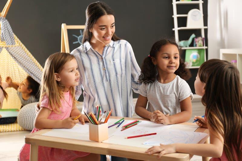 Crianças pequenas bonitos com o desenho do professor do berçário na tabela no jardim de infância fotografia de stock