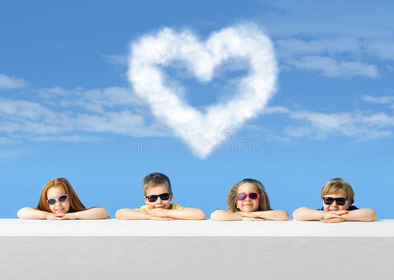 Crianças pequenas bonitos com um coração gigante da nuvem fotos de stock royalty free