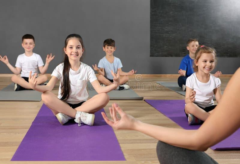 Crianças pequenas bonitos e instrutor que fazem o exercício físico no gym da escola imagem de stock royalty free