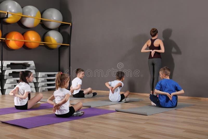 Crianças pequenas bonitos e instrutor que fazem o exercício físico no gym da escola fotos de stock royalty free