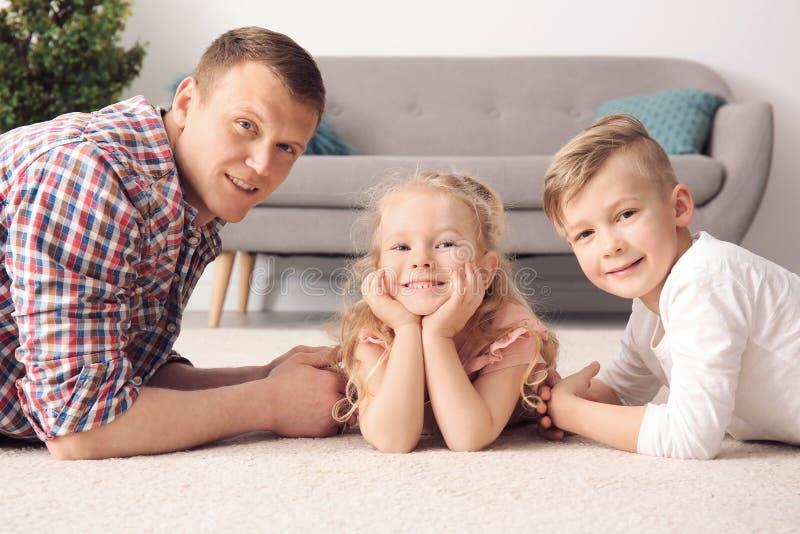 Crianças pequenas bonitos e seu pai que encontram-se no tapete acolhedor imagem de stock