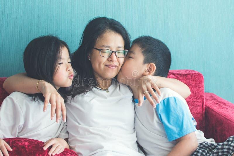 Crianças pequenas bonitos que beijam sua mãe no sofá em casa fotografia de stock royalty free