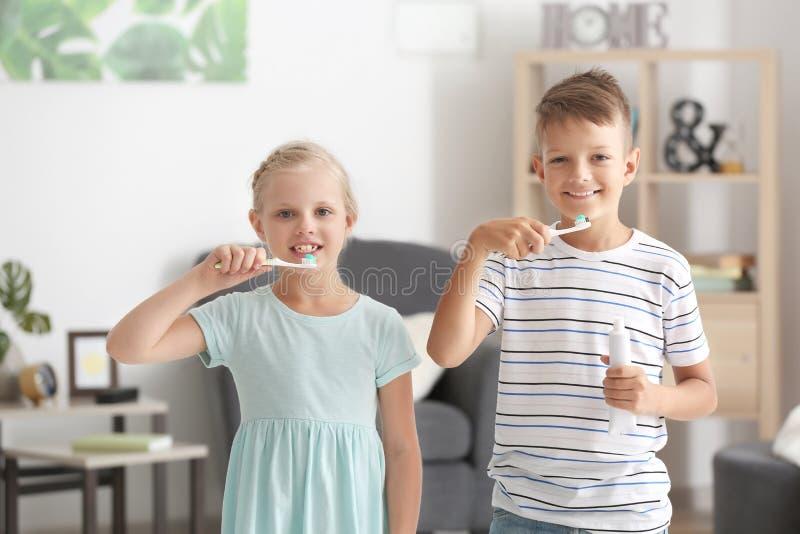 Crianças pequenas bonitos que escovam os dentes em casa fotografia de stock