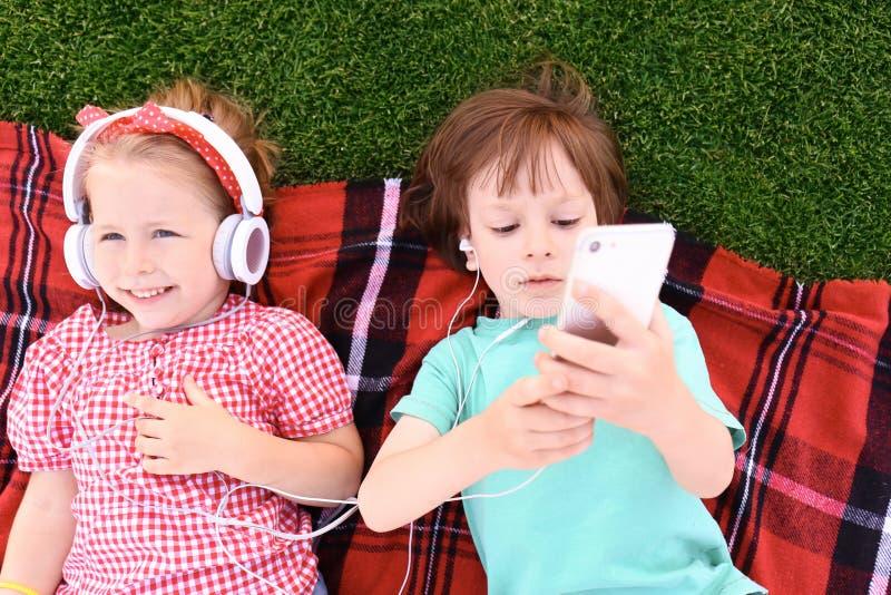 Crianças pequenas bonitos que escutam a música na manta fora fotografia de stock