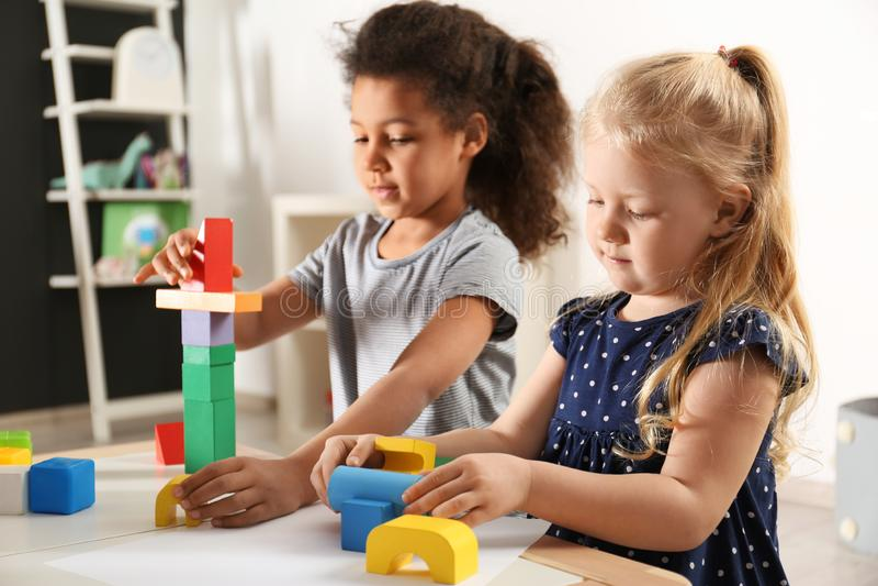 Crianças pequenas bonitos que jogam com blocos de apartamentos no jardim de infância imagem de stock royalty free