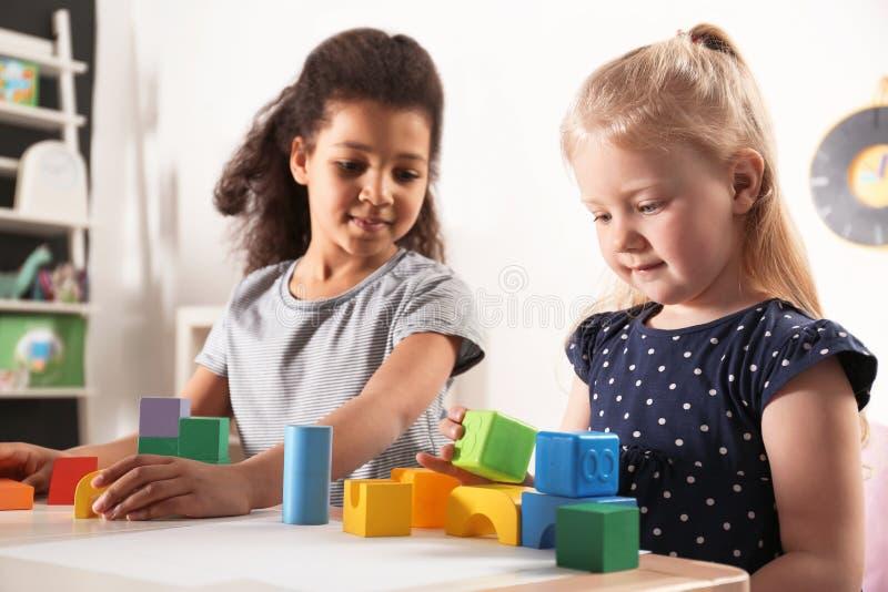 Crianças pequenas bonitos que jogam com blocos de apartamentos no jardim de infância foto de stock royalty free