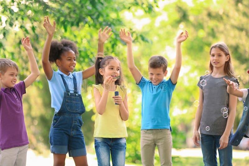 Crianças pequenas bonitos que jogam com bolhas de sabão fora imagem de stock