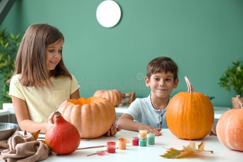 Crianças pequenas bonitos que preparam abóboras para Dia das Bruxas em casa foto de stock