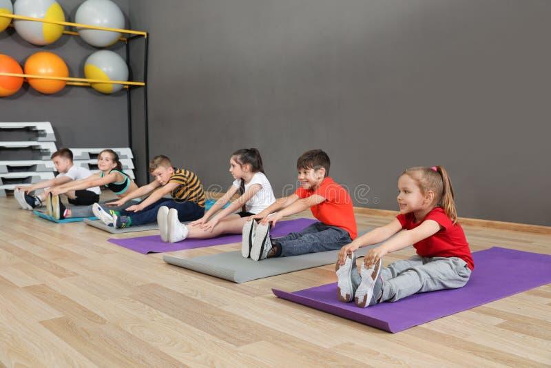 Crianças pequenas bonitos que sentam-se no assoalho e que fazem o exercício físico Estilo de vida saud?vel foto de stock