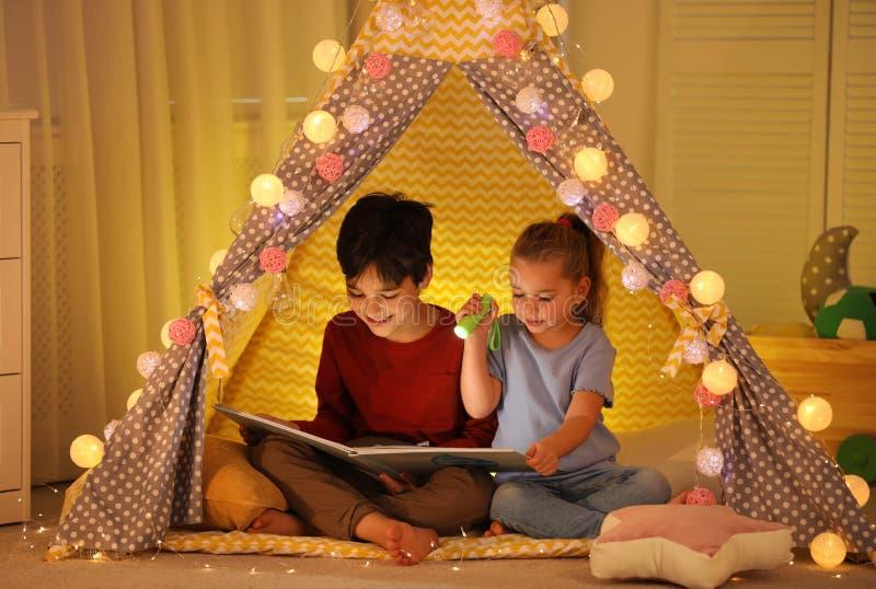 Crianças pequenas com livro de leitura de lanterna fotos de stock