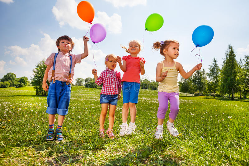 Crianças pequenas com os quatro balões no prado verde fotos de stock royalty free