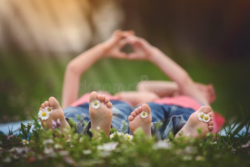 Crianças pequenas felizes, encontrando-se na grama, descalça, aro das margaridas fotos de stock