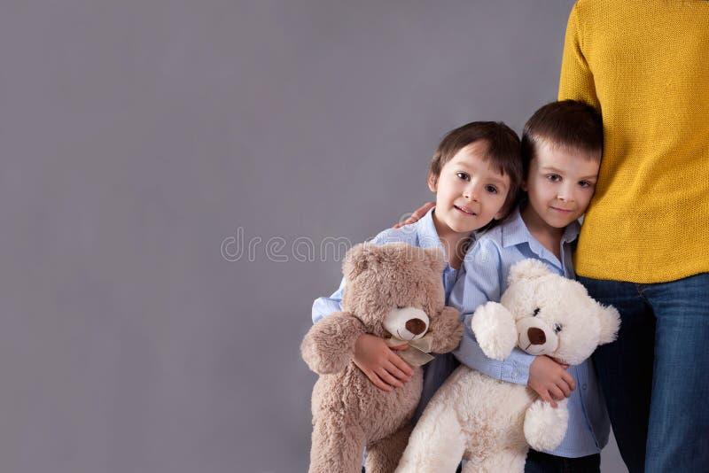 Crianças pequenas felizes, meninos, abraçando sua mãe em casa, isola foto de stock