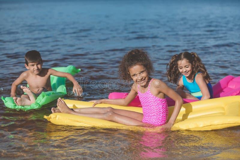 crianças pequenas multi-étnicos que nadam em colchões infláveis coloridos foto de stock