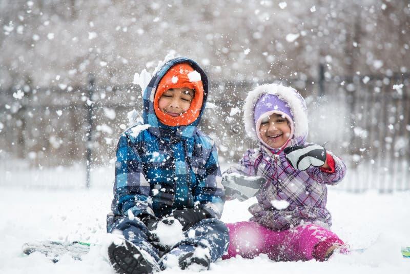 Crianças pequenas que apreciam a queda de neve fotos de stock