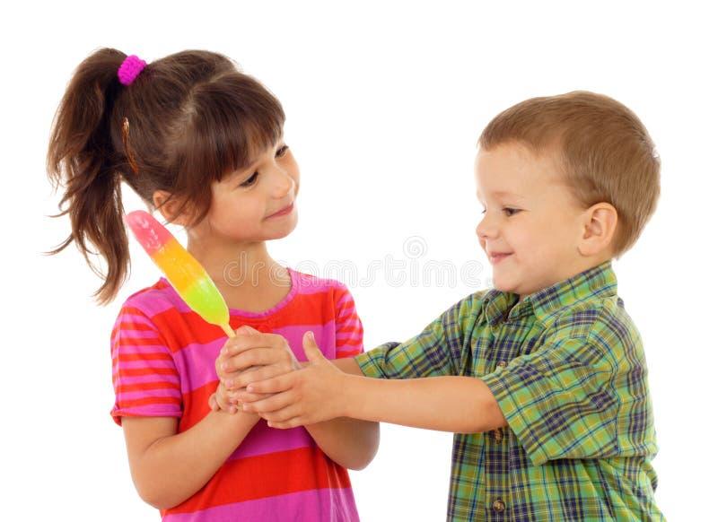 Crianças pequenas que compartilham do gelado da cor fotos de stock