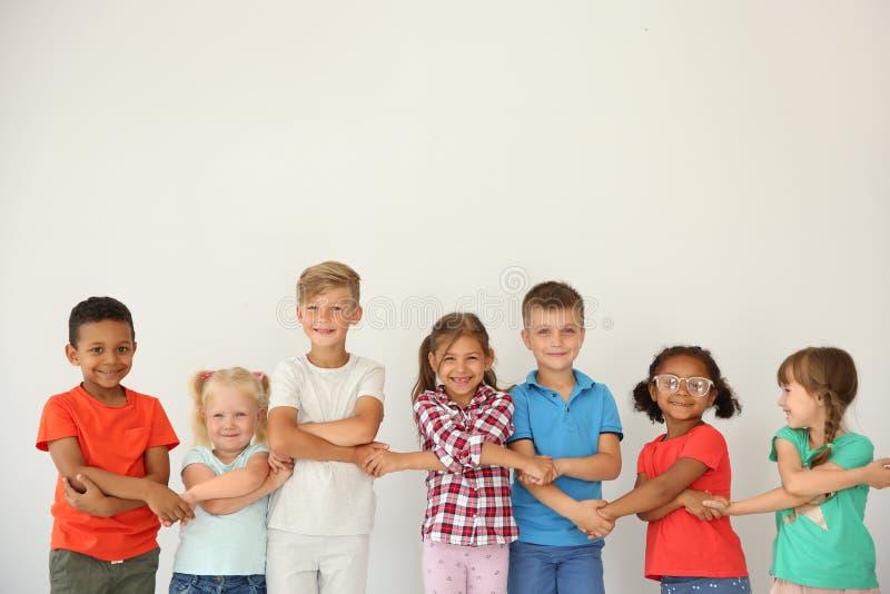 Crianças pequenas que guardam as mãos no fundo claro fotos de stock royalty free