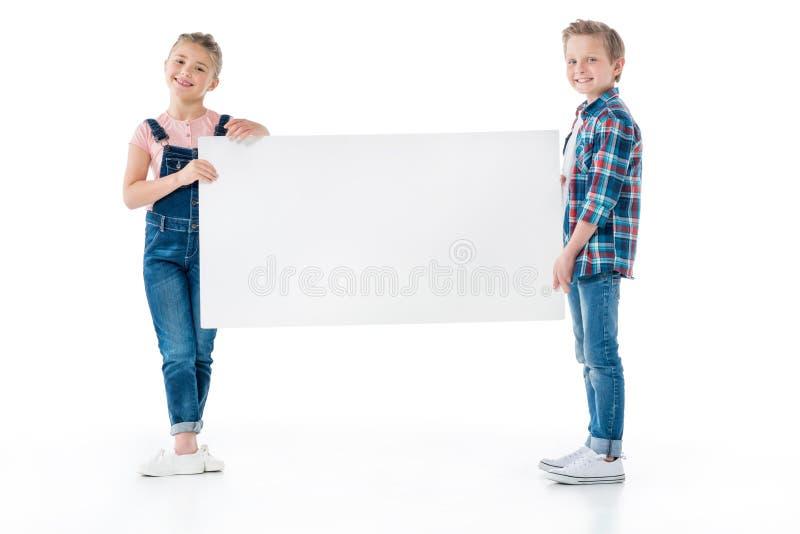 Crianças pequenas que guardam a bandeira vazia e que sorriem na câmera imagem de stock