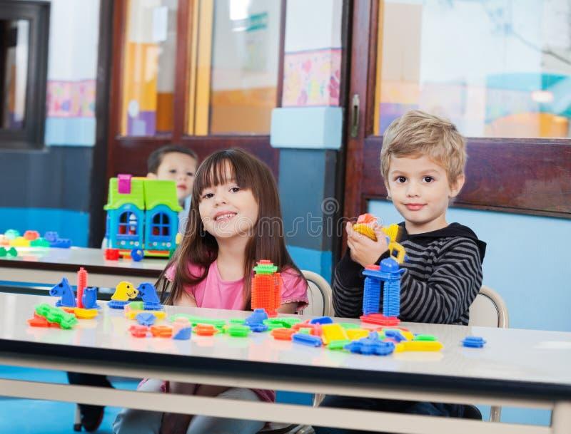 Crianças pequenas que jogam com blocos no pré-escolar foto de stock