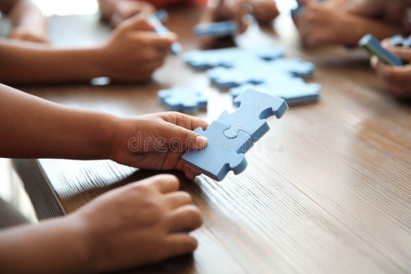 Crianças pequenas que jogam com enigma na tabela, foco nas mãos foto de stock royalty free