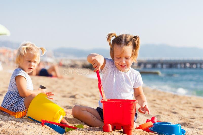 Crianças pequenas que jogam no mar foto de stock