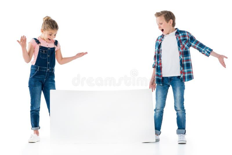 Crianças pequenas que olham o cartaz vazio isolado no branco fotos de stock royalty free