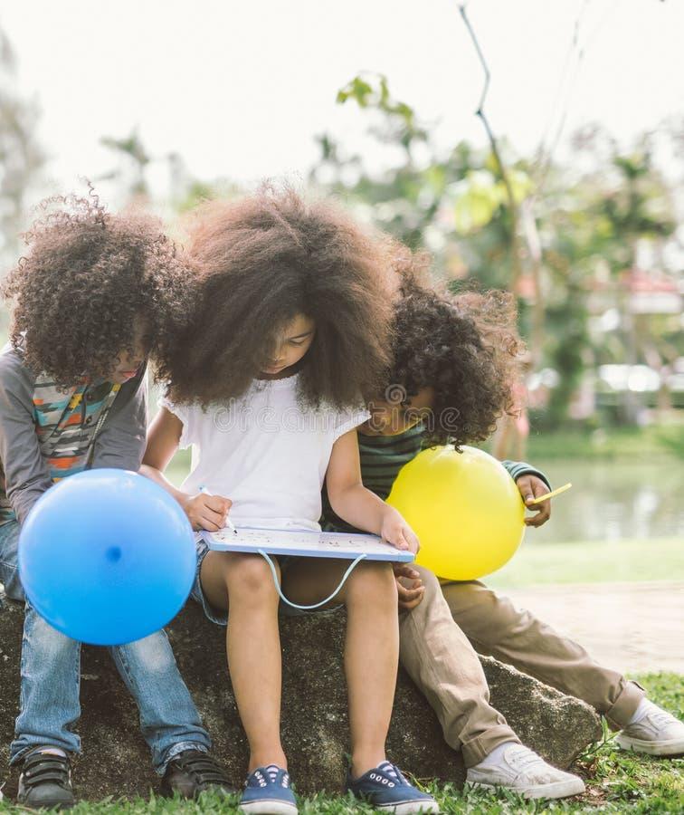 Crianças pequenas que tiram o esboço no parque imagens de stock royalty free