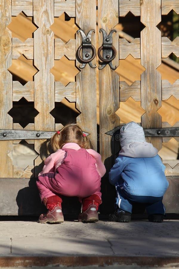 Crianças perto das portas de madeira fotos de stock