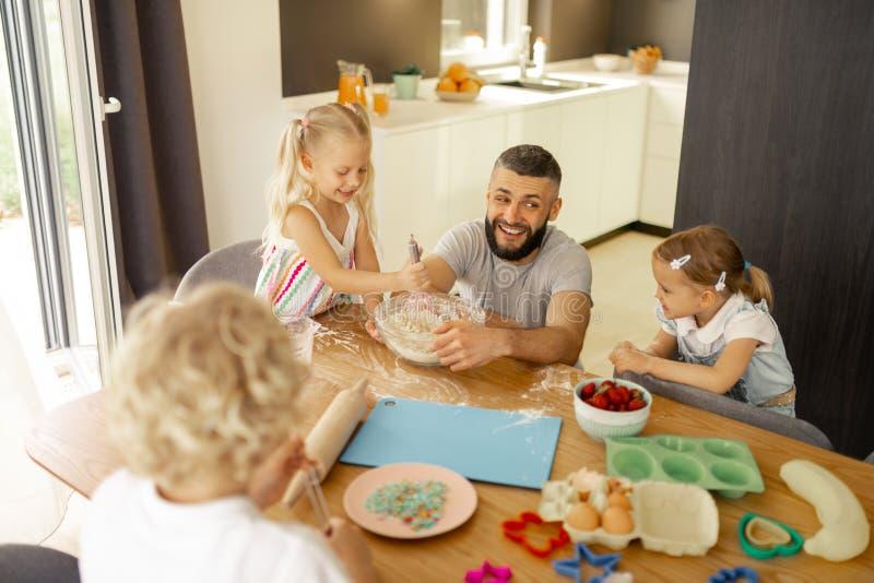 Crianças positivas deleitadas que têm o divertimento na cozinha foto de stock