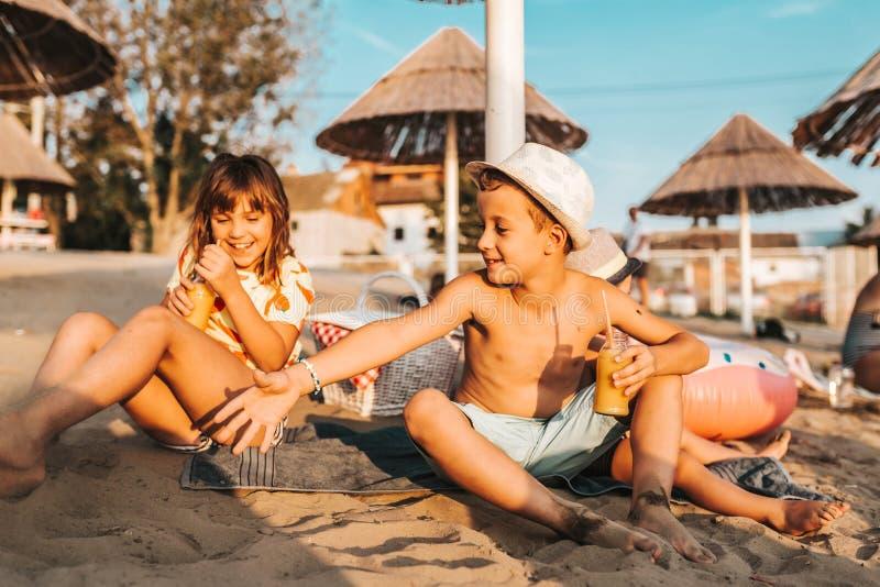 Crianças positivas felizes que têm o divertimento e que jogam na praia fotos de stock