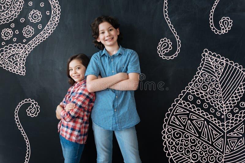 Crianças positivas que estão com seus braços cruzados e sorriso foto de stock