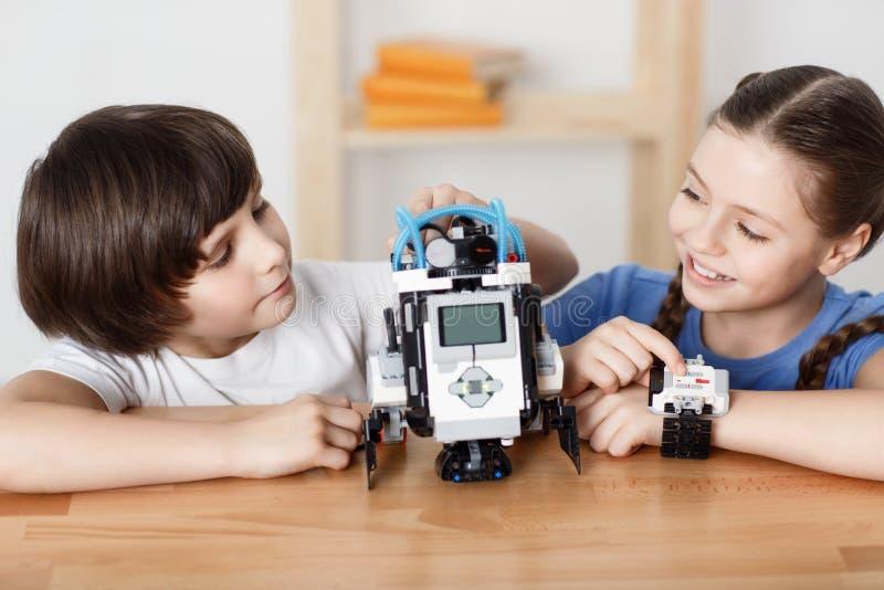 Crianças positivas que jogam com robô fotos de stock royalty free