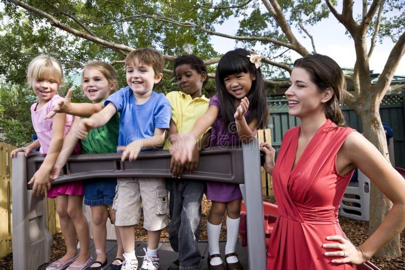 Crianças prées-escolar no campo de jogos com professor fotos de stock royalty free