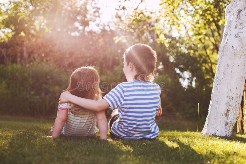 Crianças que abraçam no jardim no por do sol Irm?o com sua irm? mais nova foto de stock