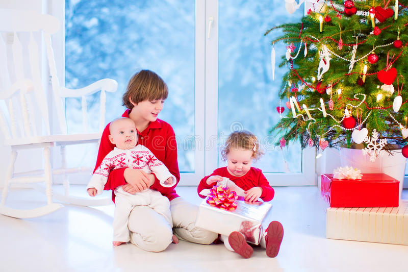 Crianças que abrem presentes de Natal imagens de stock royalty free
